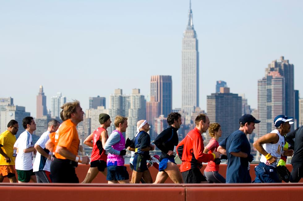 Corredores da Maratona de Nova York passam por uma das pontes do percurso, com Manhattan ao fundo